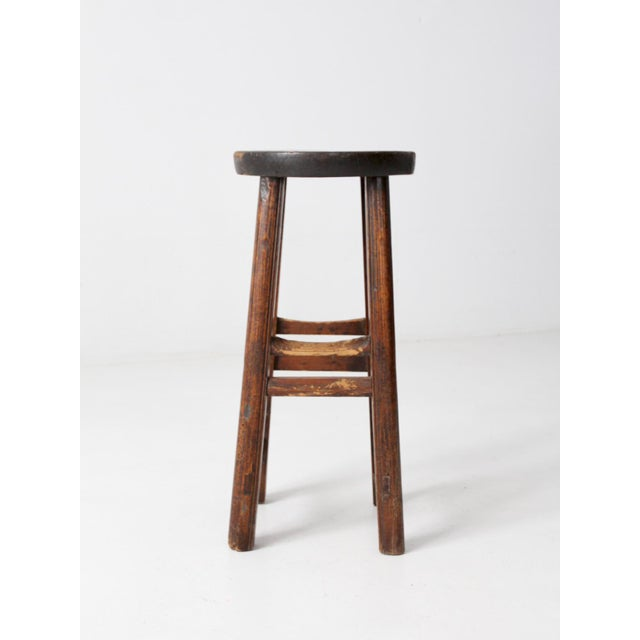 This is an antique Chinese stool. The tall wooden stool features a round seat and doubled wooden stretchers.