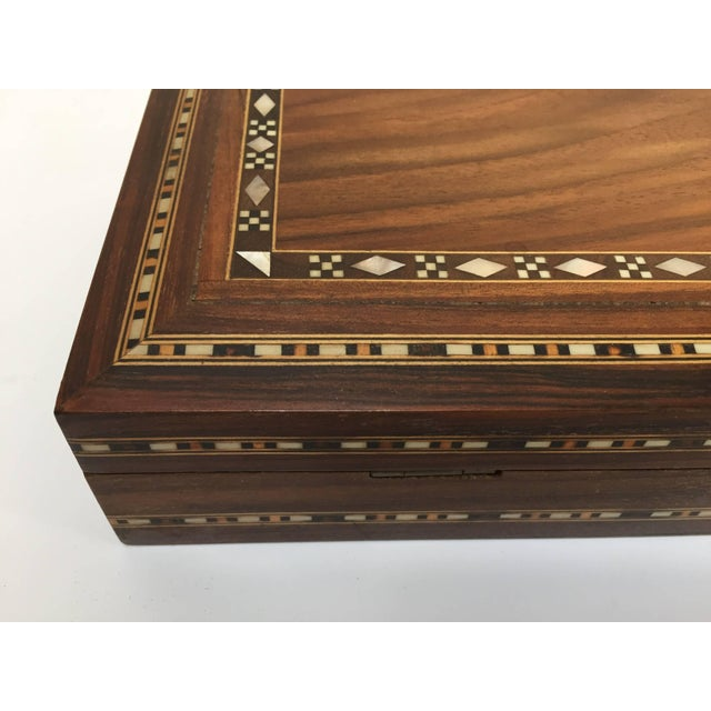 Large Middle Eastern precious wood decorative box inlay with fruitwood and mother-of-pearl and lined with red velvet. Very...