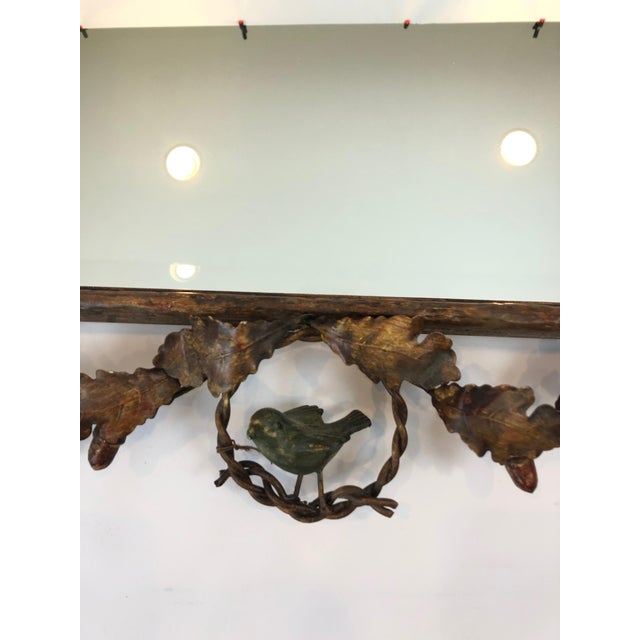 A charming gilt metal faux bois mirror having delightful leaf and acorn decoration and a green painted bird perched on the...