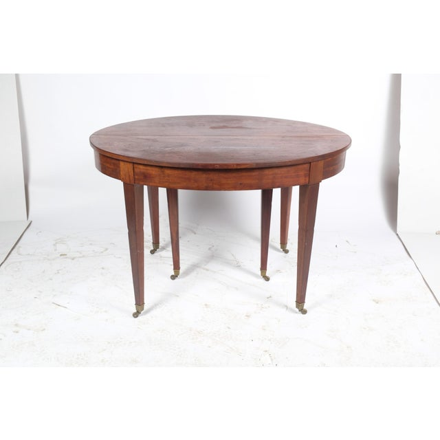 French Louis XVI-Style oval mahogany center table library/dining table featuring brass ferrules on feet. Table does extend...