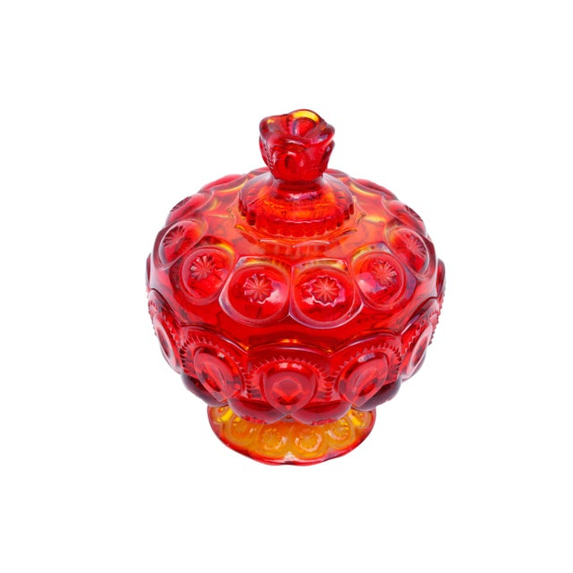 A lidded glass candy dish made by L.E.Smith. Decorated with the 'Moon & Stars' pattern in the Amberina color - a bright...