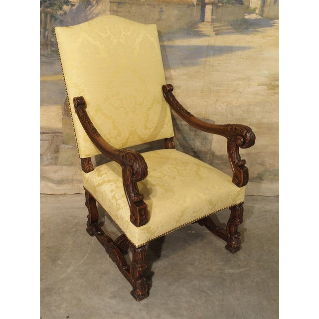 This highly carved antique French fauteuil (armchair) is made from walnut wood. Scrolling floral and foliate acanthus leaf...