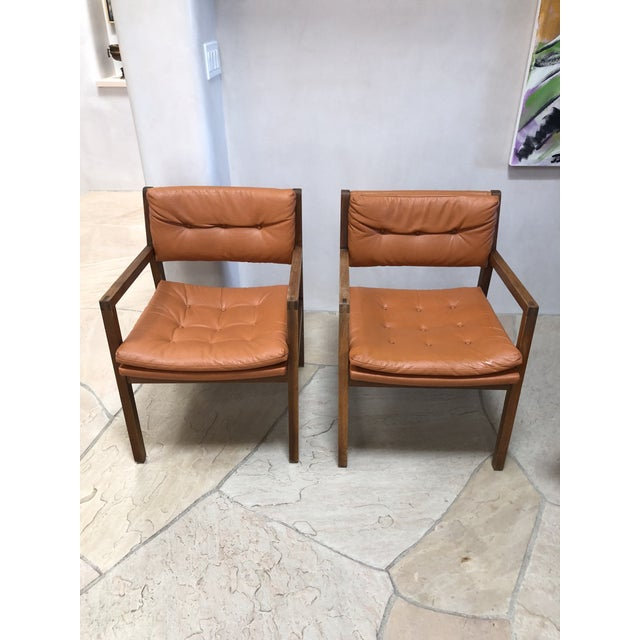 A pair of mid Century Modern leather chairs made in the USA by Indiana Chair Company. The leather is burnt orange and the...
