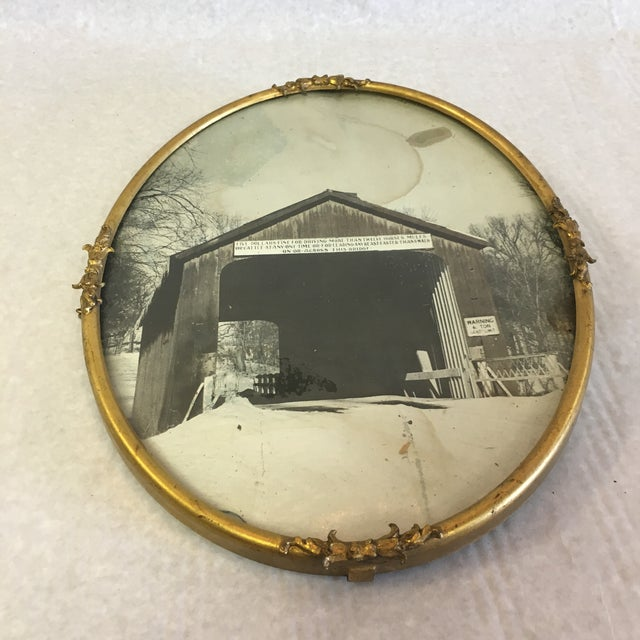A vintage photo of a covered bridge in a round brass frame.