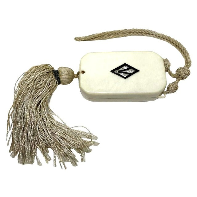 Circa 1920s celluloid vanity purse with a faux-ivory pattern, embellished with a black diamond motif set with clear...