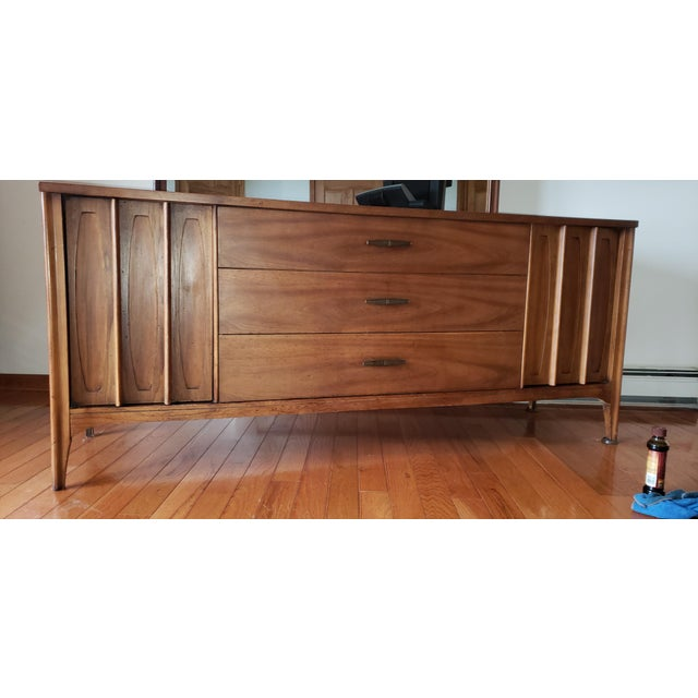 Dark walnut long dresser. Some damage to one bar on left side door and minor darker coloration on surface as shown in...