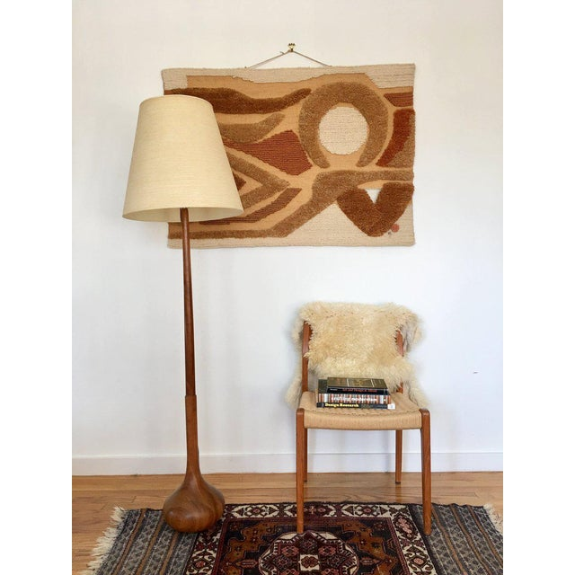 Sleek Scandinavian Modern teak floor lamp features a long, slender, slightly tapered neck ending in an organic form...