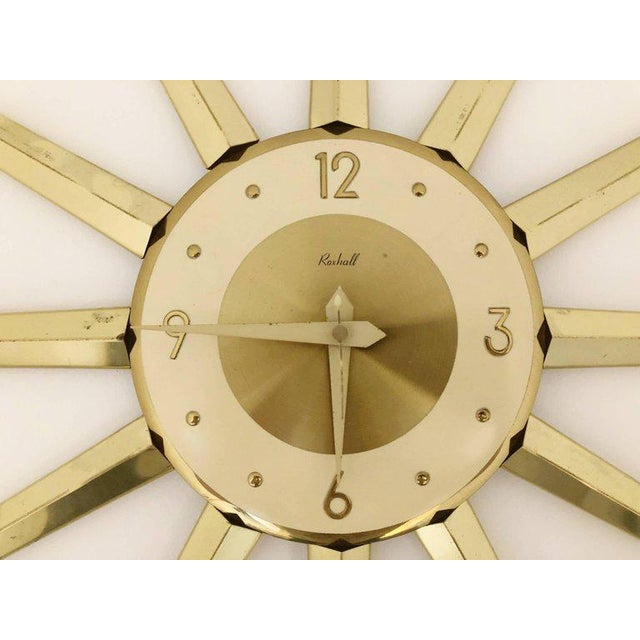Large spike starburst clock by Roxhall. Featuring gleaming brass colored metal sunburst points with a brushed brass...