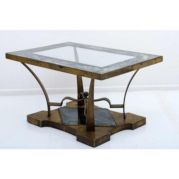 For your consideration a vintage brass side table with eglomized glass on top and bottom. Sculptural and unique shape....
