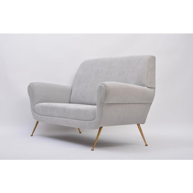 This sofa was designed by Gigi Radice for Minotti in the 1950s. It has been newly upholstered and features brass legs.