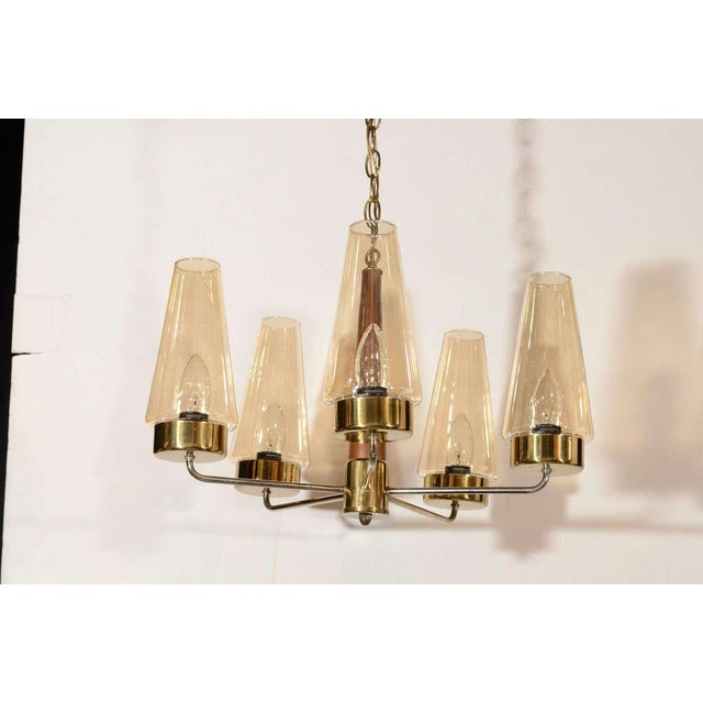 Vintage mid-century modern chandelier from Denmark with five light radial design. Features teak wood stem with brass arms,...