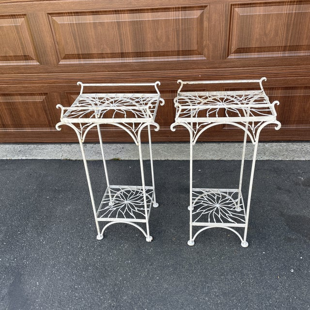 Pair of white metal plant stands with flower design tops and shelves. Wonderful patina. These would also do well as accent...