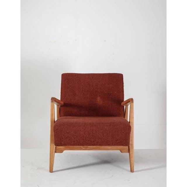 A comfortable lounge chair by Jens Risom with a walnut frame and integrated cushions with a red-brown wool upholstery....
