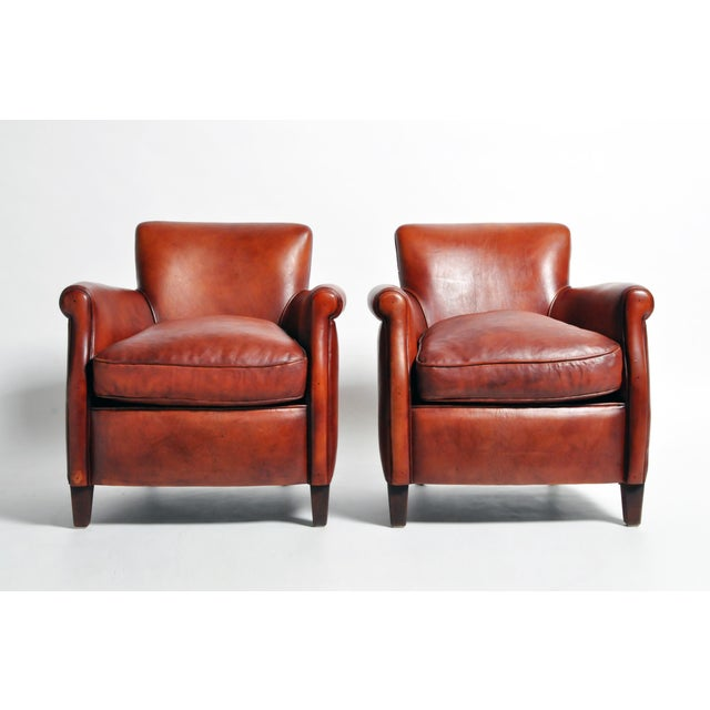 This pair of armchairs are from France and made from leather and wood, circa 21st century. They are newly made and feature...