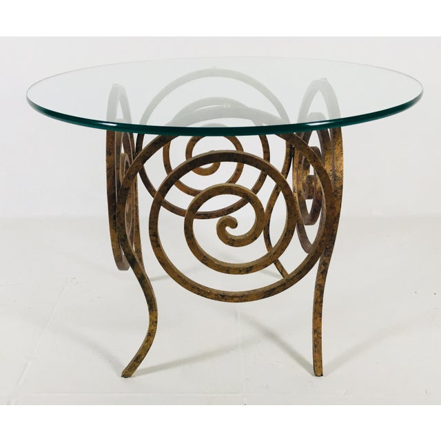 This is a mid Century modern glass and wrought iron coffee table in a gold scroll pattern. The base is approx 25lb, Circa...