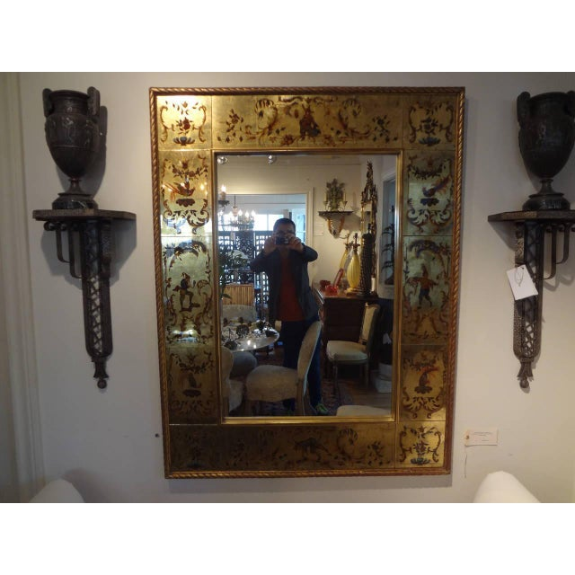 Chic French reverse painted rectangular gilt eglomise mirror with Commedia dell'Arte design border. This Chinioserie...