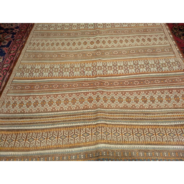 The Uzbek Kilim from Central Asia has rows of different designs if cream, brown and orange colors. Dimensions: 3′ 7″ x 6′...