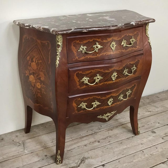 Antique French Louis XV Bombe Marquetry Marble Top Commode combines the talents of an expert cabinet maker able to create...