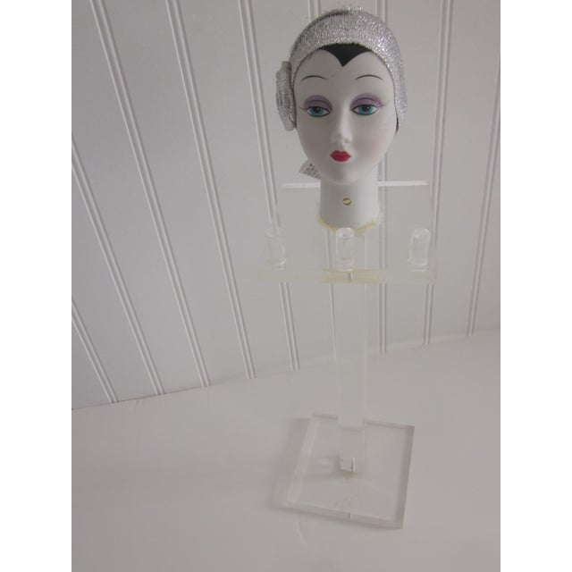 A vintage, 1985 Bisque doll head mannequin lucite display piece. It has three pegs for dangling necklaces. The doll is...