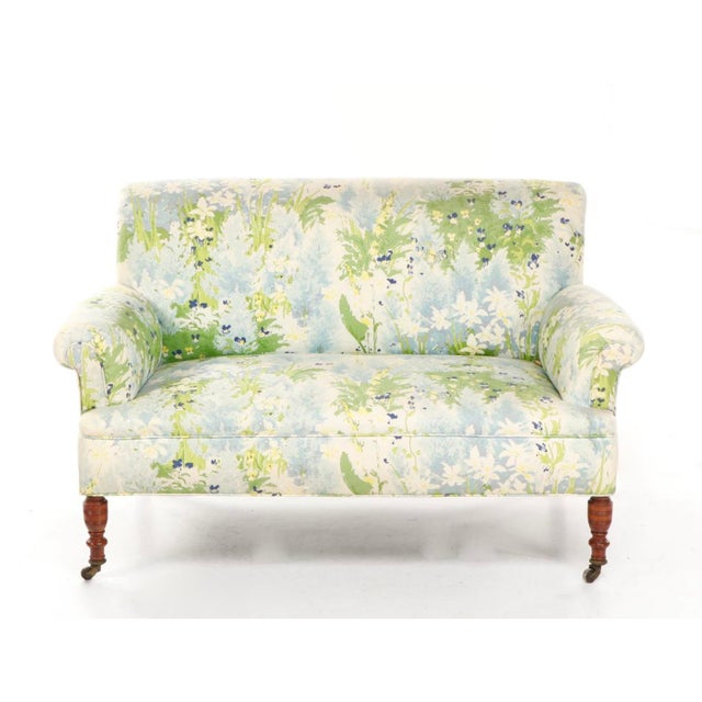A stylish vintage loveseat or settee in lovely floral upholstery and wooden feet with casters, France, circa 1940s. The...