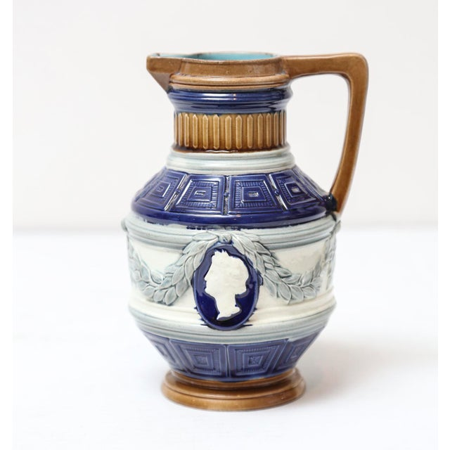Early 20th-Century English antique majolica pitcher with cobalt blue and cameo portraits encircled with laurel leaves. A...