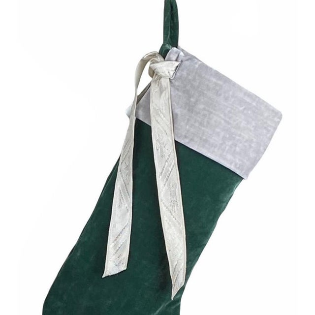 Custom green French velvet stocking with removable silver velvet collar and vintage French jacquard ribbon. The stocking...
