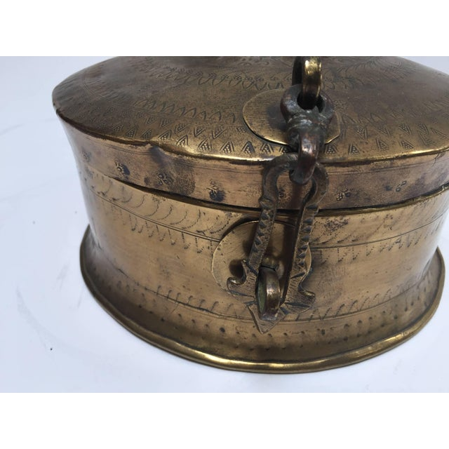 Handcrafted decorative round brass Anglo Indian lidded box with latch and a top handle. Delicately and intricately hand-...