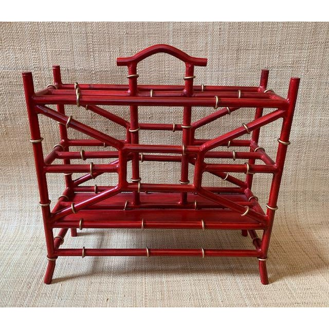 Magazine rack in the manner of Maison Bagues. Hollywood Regency style crafted to look like bamboo. Painted red with gold...