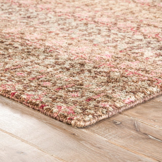 Jute lends natural texture to this exquisitely made hand-knotted area rug. Bold tones of pink, red, and brown enrich the...