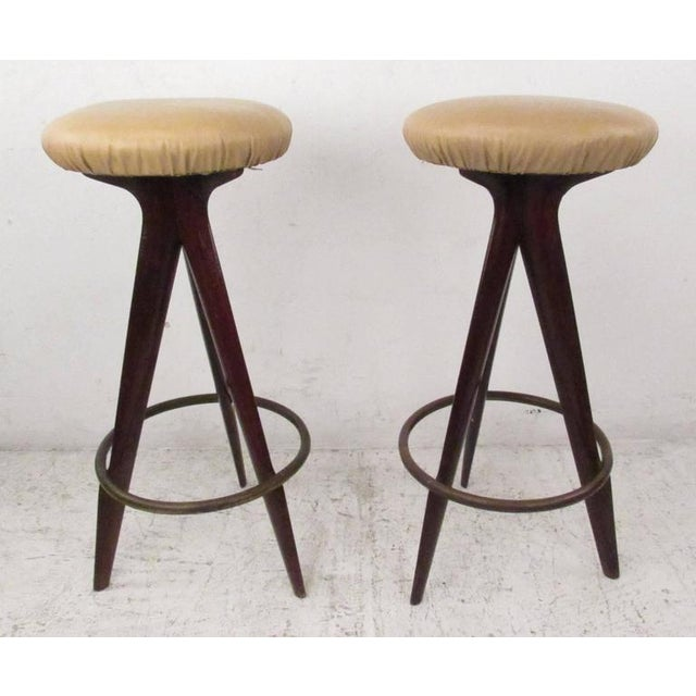 Stylish pair of three leg mahogany stools with brass foot rest and vinyl seats. Please confirm item location (NY or NJ)...
