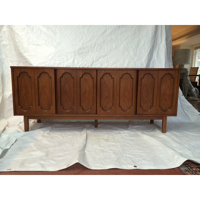 Long, solid wood buffet made by Dixie Furniture Co. Includes four doors, the center two doors open to reveal three...