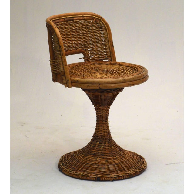 In the manner of Franco Albini, circa 1955 is a dining table and two tiki swivel chairs in wicker rattan. Measures: Table...