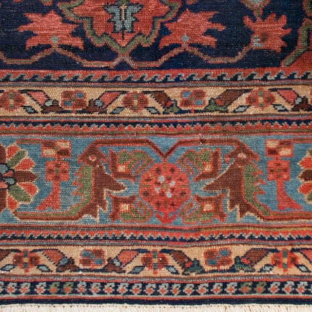 A 19th century Persian Nahavand carpet with three red central floral medallions on surrounded by green scrolling vines...