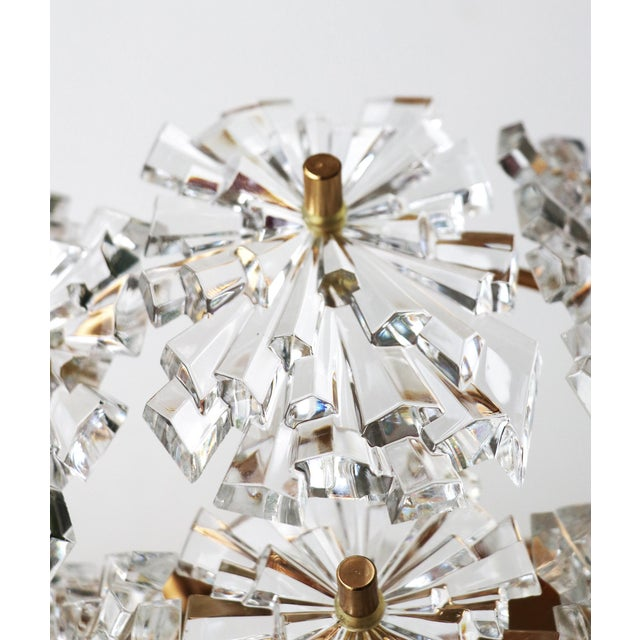 Elegant pair of starburst crystal glass wall sconces, each with ten faceted crystals mounted on gold-plated brass frame....