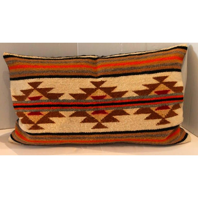 This is a single saddle blanket pillow with vibrant colors and design. The backing is in a dark brown cotton linen.