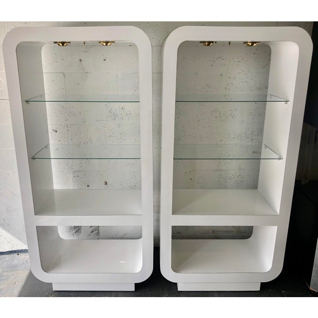 This is a fantastic pair of white mica covered etageres. There are two glass shelves and two wood shelves covered with...