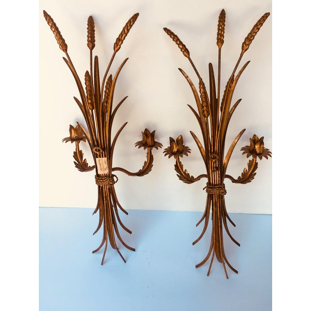 This Hollywood Regency pair of sconces was hand crafted in Italy. They are made of iron with a mellow gold finish. The...