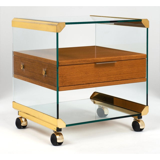 A fun brass and glass modernist side table / night stand featuring one dovetailed drawer. There is a glass structure...