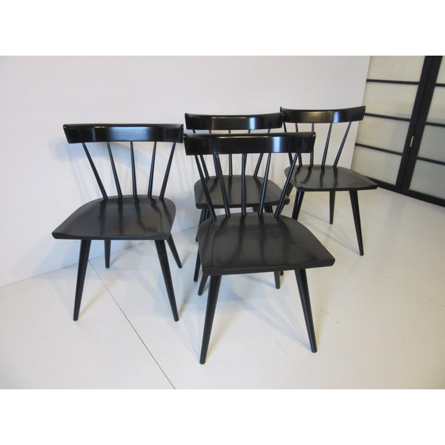 A set of four satin black McCobb solid maple spindle back dining chairs from the Planner Group Collection retaining the...
