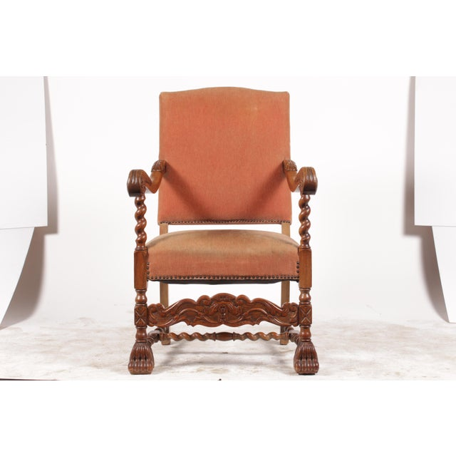 1920s English Baroque-style armchair featuring oak barley twist arms, salmon velvet upholstery with nailhead trim and paw...