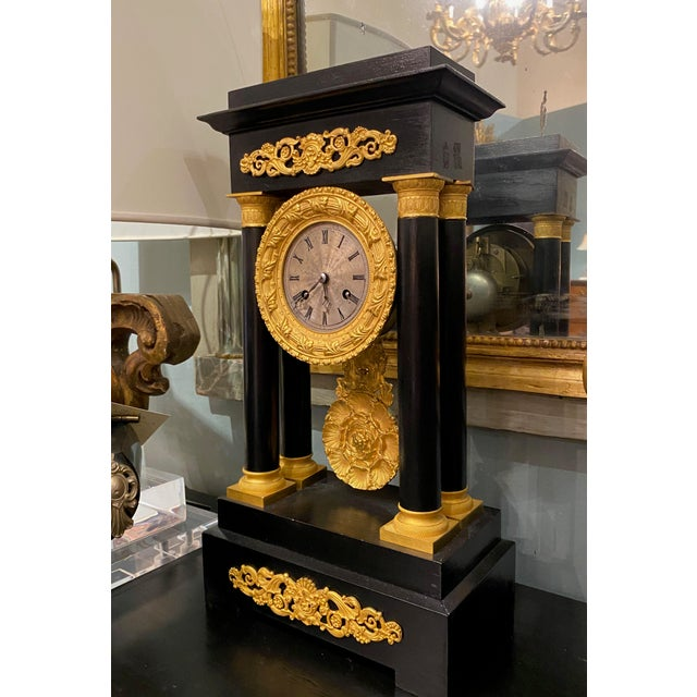 An antique black and gold French portico mantel clock with beautiful details. The clock is signed on back and has its key....