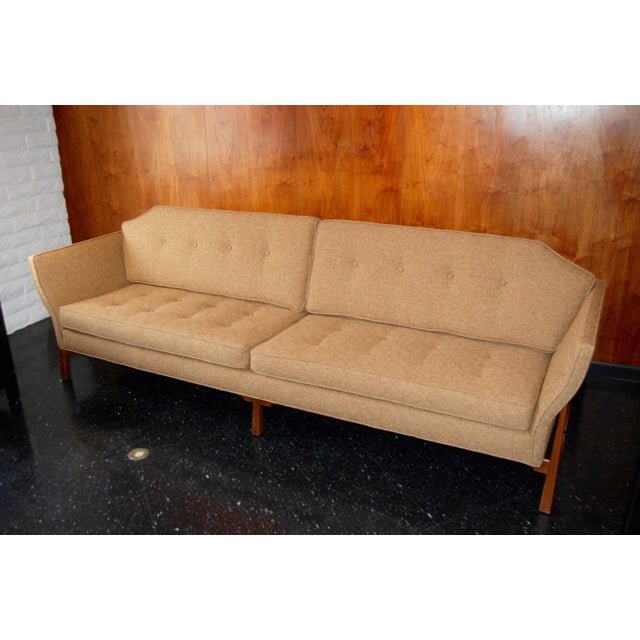 Mid-Century Modern Dunbar sofa with a uniformly tufted back and loose cushions. Recently reupholstered with newly...