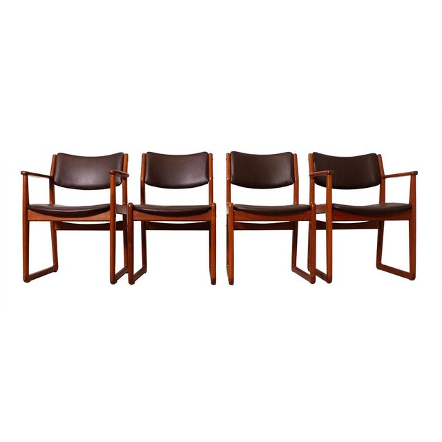 Handsome set of four dining chairs with a teak frame and fully upholstered back and upholstered seat. A cross bar connects...