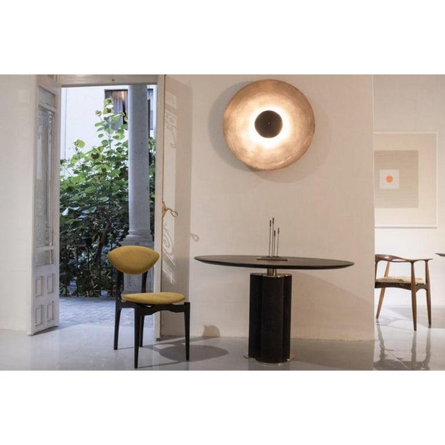 The Cinta dining table is a Charcoal oiled walnut table top with charred linear textured base and brass details. The...