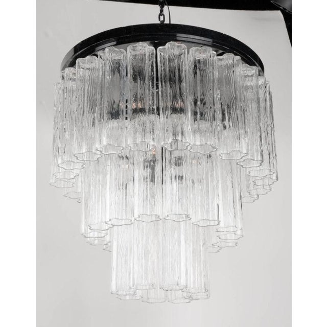 A glass tube chandelier comprising a round, black enameled steel plafonnier that supports a metal frame containing three...
