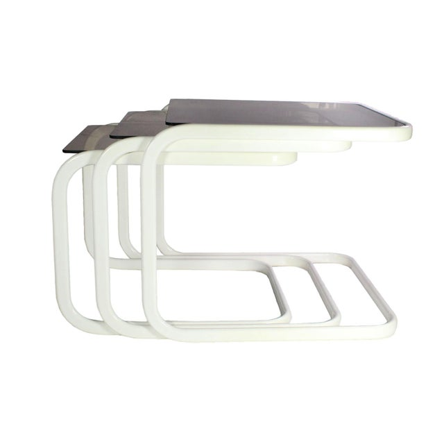 Set of three white coated brass and smoked glass nesting tables attributed to Milo Baughman for Design Institute of...