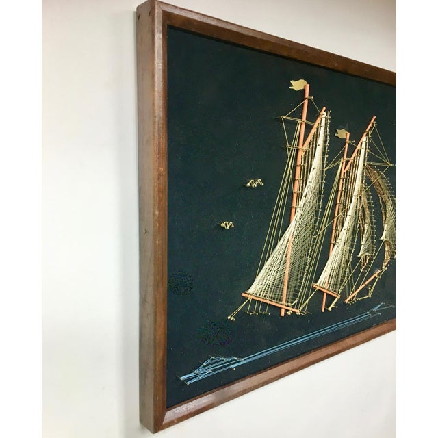 An intricate, intricate and tasteful pieces of string art of a sailing ship rendered in brass pieces, brass nails,...