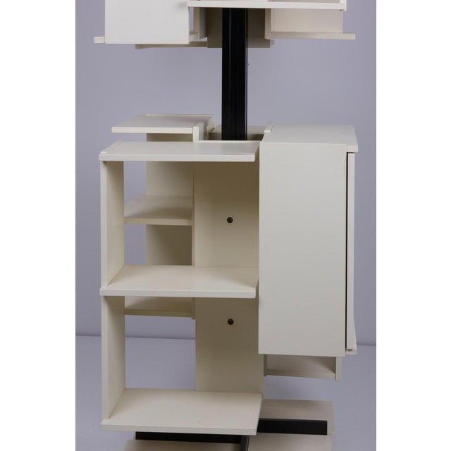 Rotating high bookshelf with seven open and one close storage compartments.