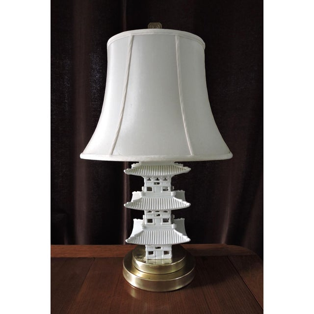 Striking three tier pagoda lamp on circular brass base. White 'blanc de chine' porcelain topped with brass oriental style...