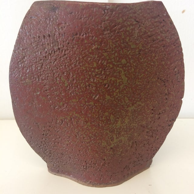 "Beautiful shaped handmade, textured vase. Features brown and maroon tones. Is signed by the artist ""Read"" on the base."